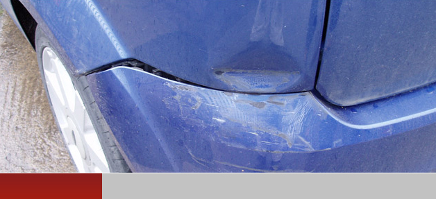 Dent in front panel of red car