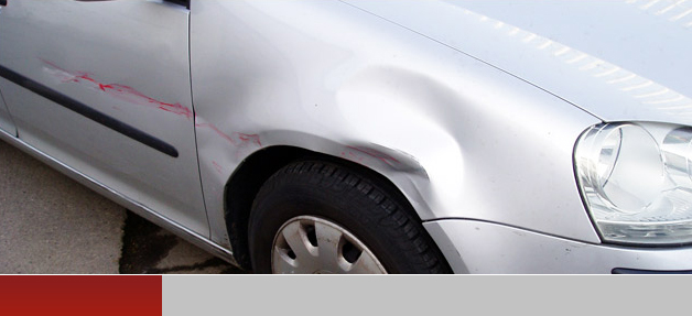 Silver car with dents in bodywork